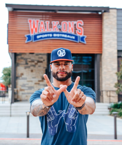 NFL Quarterback Dak Prescott does the W hand sign in from of a Walk-On's restaurant wearing the navy WIN tee and the W snapback hat.