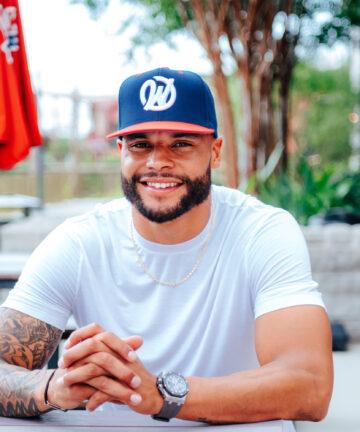 NFL Quarterback Dak Prescott wears the W hat while sitting at a table. Dak is smiling.